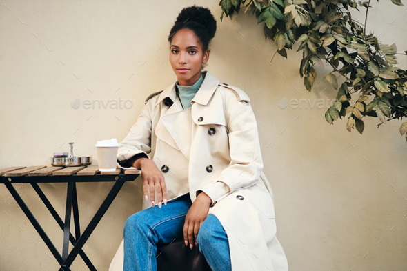 Beautiful African American girl in stylish trench coat sensually looking in camera in cafe on street - Stock Photo - Images