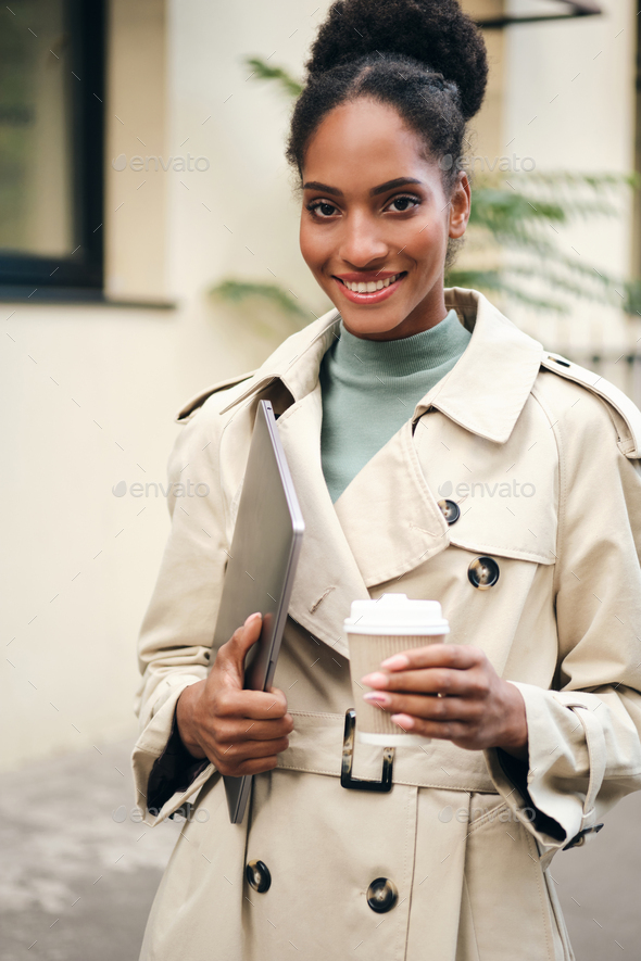 African American business woman in stylish trench coat happily looking in camera on city street - Stock Photo - Images