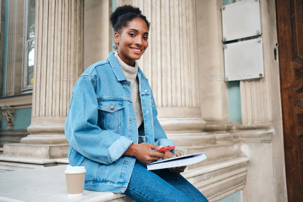 African American student girl in denim jacket with cellphone and book happily looking in camera - Stock Photo - Images