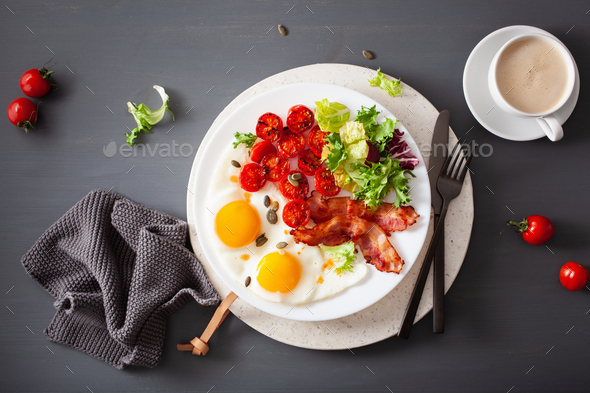 healthy keto breakfast: egg, tomatoes, salad leaves and bacon - Stock Photo - Images