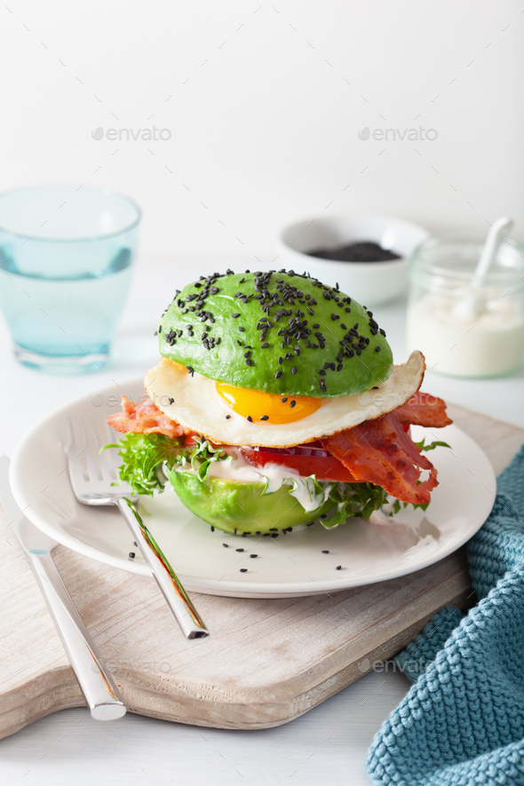 keto paleo diet avocado breakfast burger with bacon, egg, tomato - Stock Photo - Images