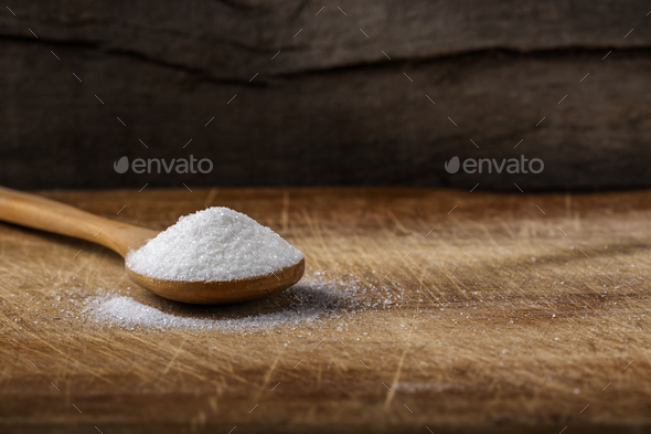 One bamboo spoon filled with white sugar - Stock Photo - Images