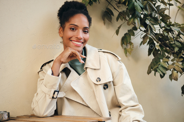 Cheerful African American girl in stylish trench coat joyfully looking in camera in cafe on street - Stock Photo - Images