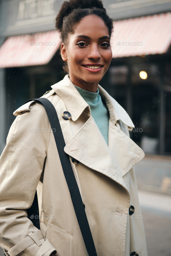 Pretty smiling African American casual girl in trench coat happily looking in camera outdoor - Stock Photo - Images