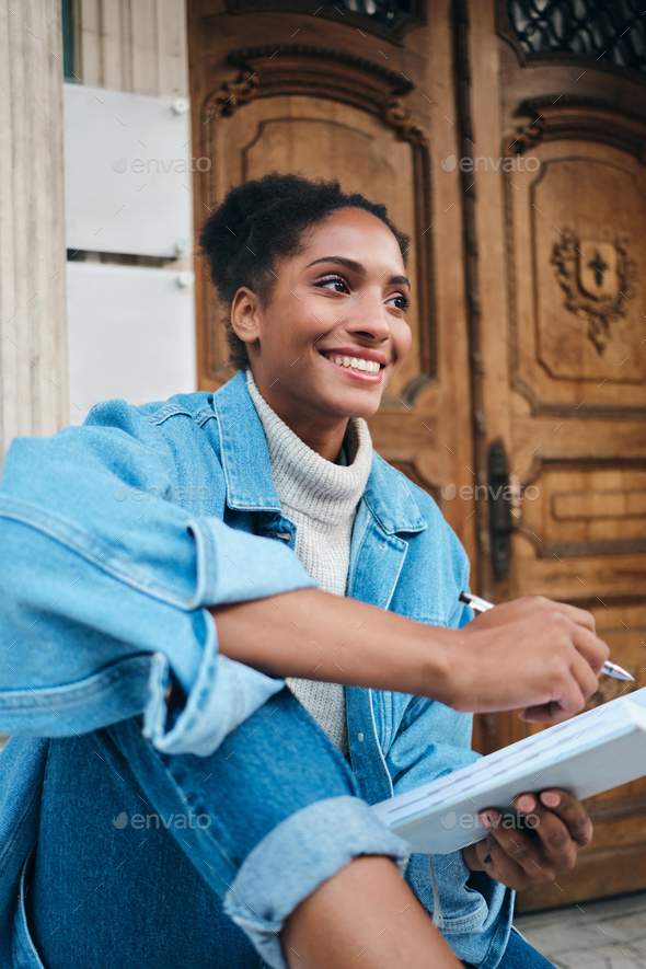 Cheerful African American student girl in denim jacket with notebook joyfully studying outdoor - Stock Photo - Images