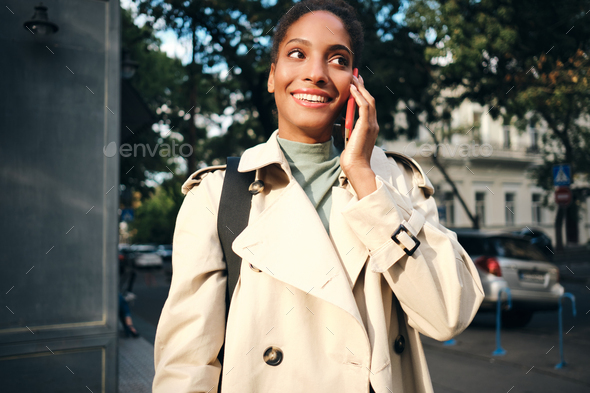 Pretty smiling African American girl in stylish trench coat happily talking on cellphone outdoor - Stock Photo - Images