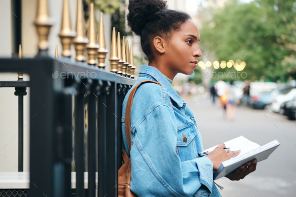 African American student girl in denim jacket with notepad thoughtfully studying on city street - Stock Photo - Images