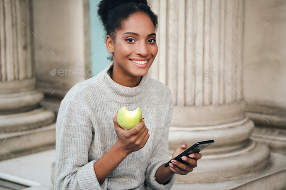 Smiling African American girl in sweater with cellphone eating apple joyfully looking in camera - Stock Photo - Images