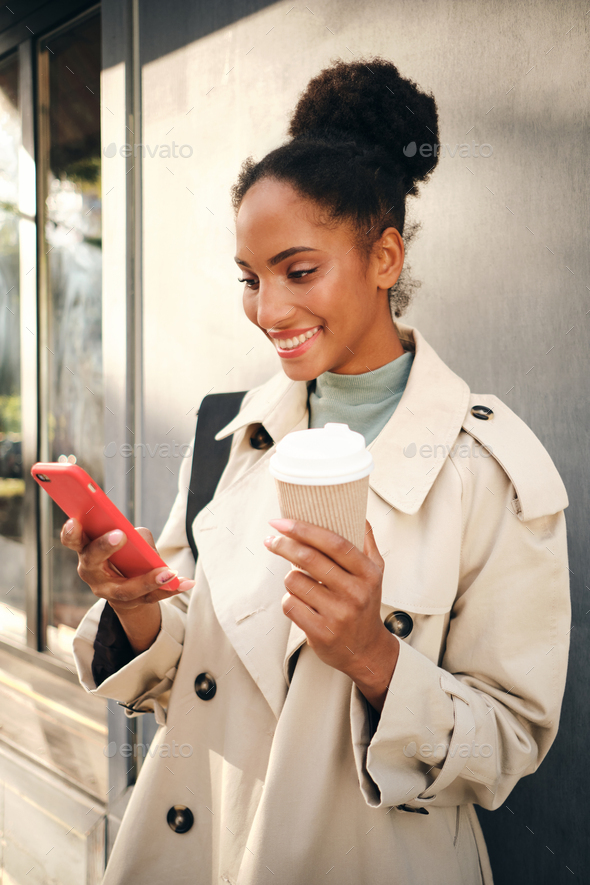 Smiling African American girl in stylish trench coat with coffee happily using cellphone outdoor - Stock Photo - Images