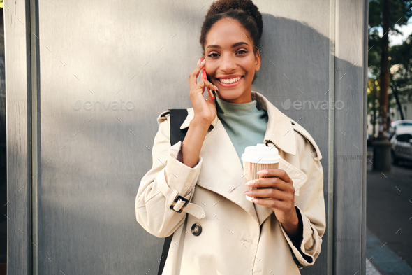 Happy African American girl in trench coat joyfully looking in camera talking on cellphone - Stock Photo - Images