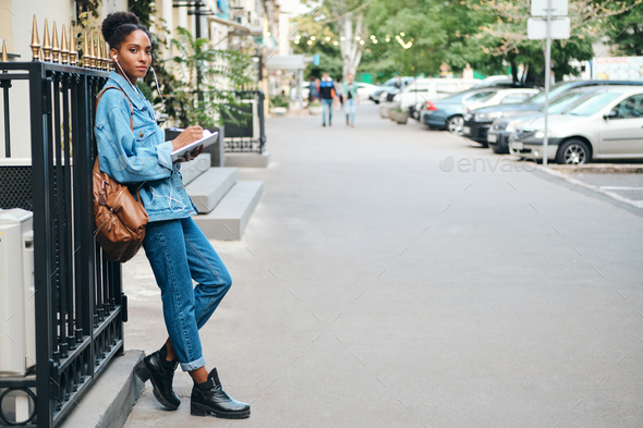 African American student girl in denim jacket with backpack confidently looking in camera on street - Stock Photo - Images