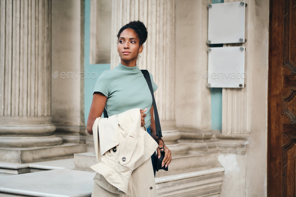Beautiful African American girl with trench coat in hand thoughtfully walking down the street - Stock Photo - Images