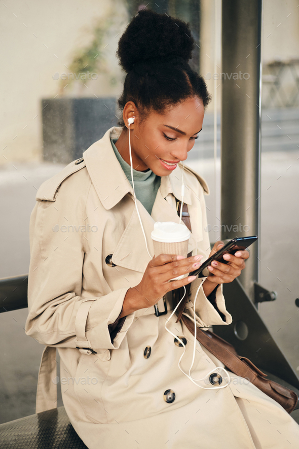 African American girl in stylish trench coat and earphones happily using cellphone at bus stop - Stock Photo - Images