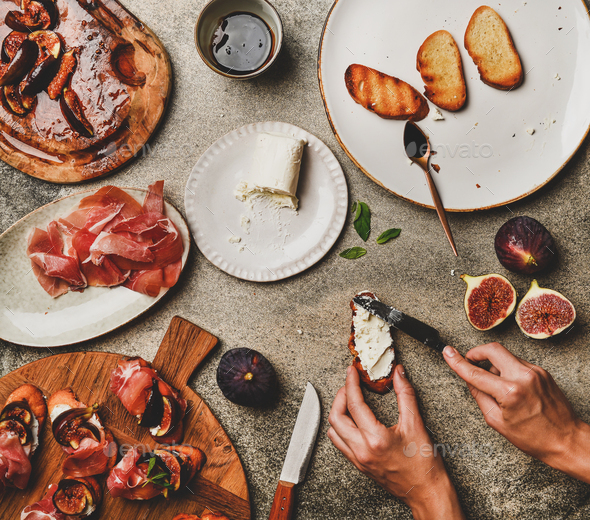 Crostini with prosciutto, figs and female hands spreading goat cheese - Stock Photo - Images