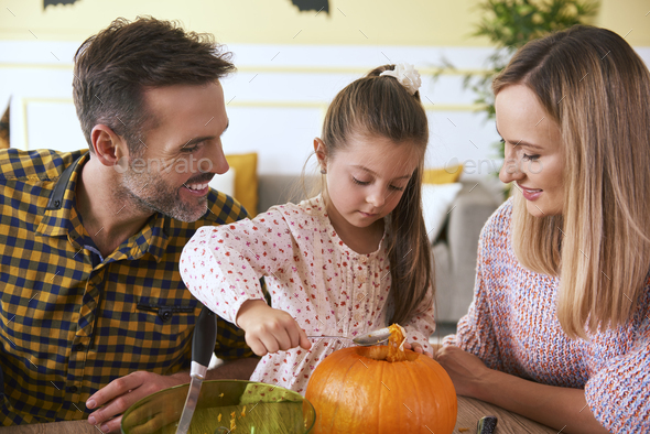 Happy family carving pumpkin for Halloween - Stock Photo - Images