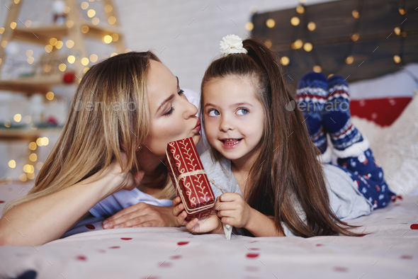 Cute girl giving christmas present to her mom - Stock Photo - Images