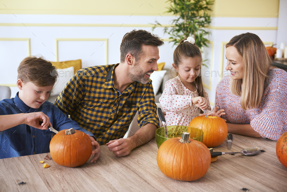 Children carving pumpkins with parents - Stock Photo - Images