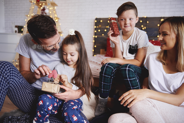 Happy family opening christmas presents in bed - Stock Photo - Images