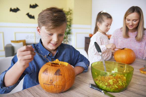 Happy boy carving pumpkin for Halloween - Stock Photo - Images