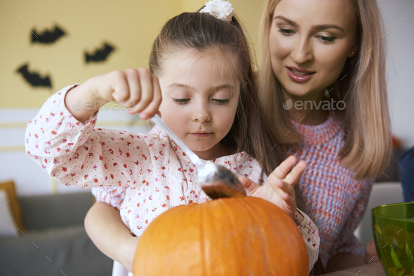 Mother and daughter working on halloween pumpkins - Stock Photo - Images
