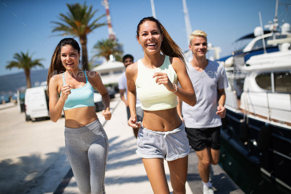 Healthy group of friends running and enjoying friend time together - Stock Photo - Images