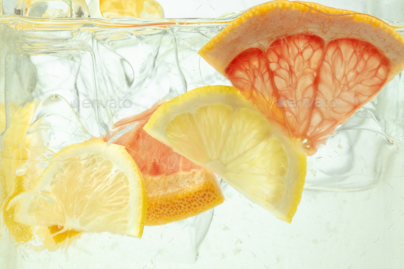 Close up view of the lemon and grapefruit slices in lemonade on background - Stock Photo - Images