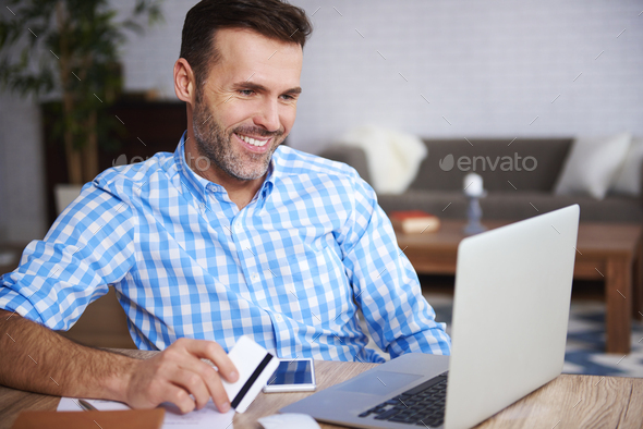 Happy man using laptop and credit card during online shopping - Stock Photo - Images
