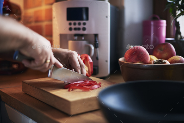 Man cutting red pepper in the kitchen - Stock Photo - Images