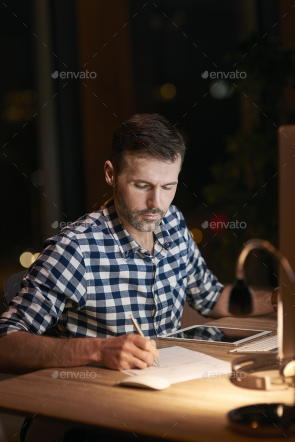 Serious man signing documents at night - Stock Photo - Images