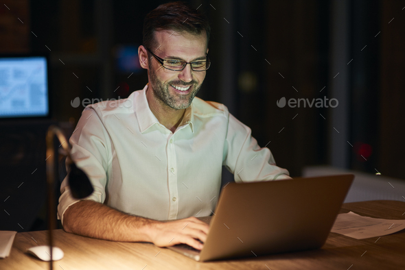 Smiling man using a laptop at night - Stock Photo - Images