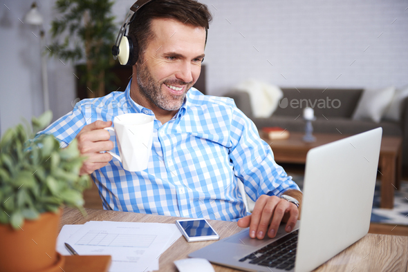 Multi tasking man working at home office - Stock Photo - Images