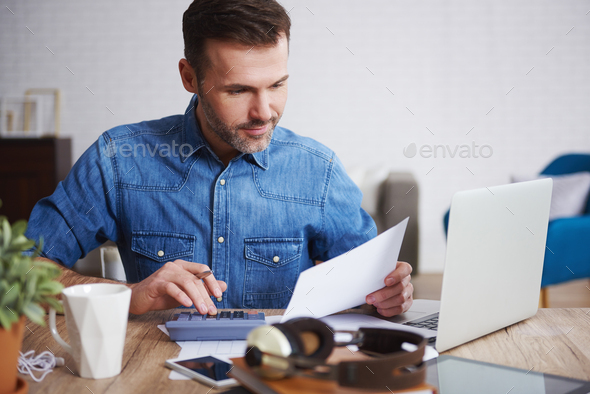 Businessman calculating his monthly expenses - Stock Photo - Images