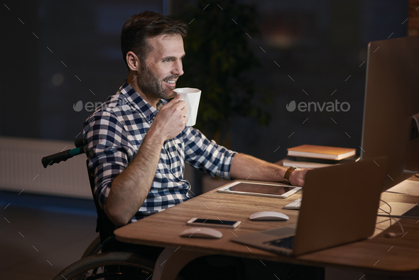 Side view of disabled businessman working late - Stock Photo - Images