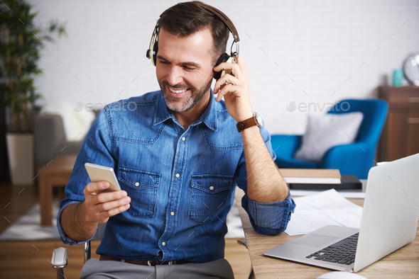 Happy man listening to music and using mobile phone - Stock Photo - Images