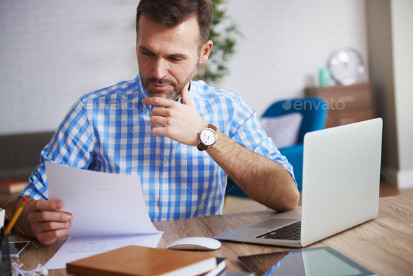 Business person reading important documents at his desk - Stock Photo - Images