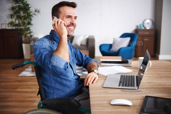 Smiling man on wheelchair talking by mobile phone in home office - Stock Photo - Images