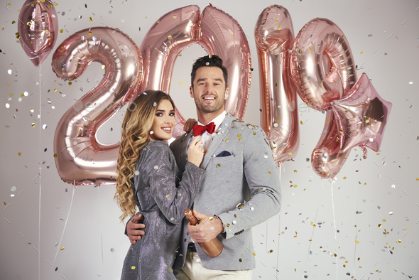 Portrait of couple with balloons and champagne under shower of confetti - Stock Photo - Images