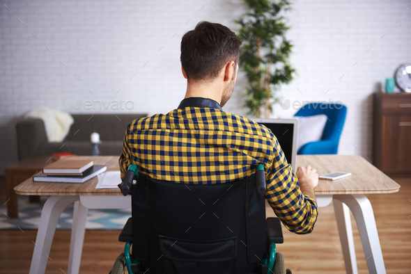 Rear view of disabled man using laptop - Stock Photo - Images