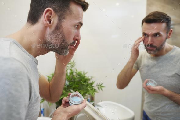 Mature man using under eye - Stock Photo - Images