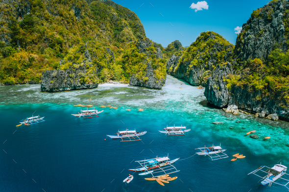 Aerial view of tourist boats in front of big Lagoon at Miniloc Island, El Nido, Palawan, Philippines - Stock Photo - Images