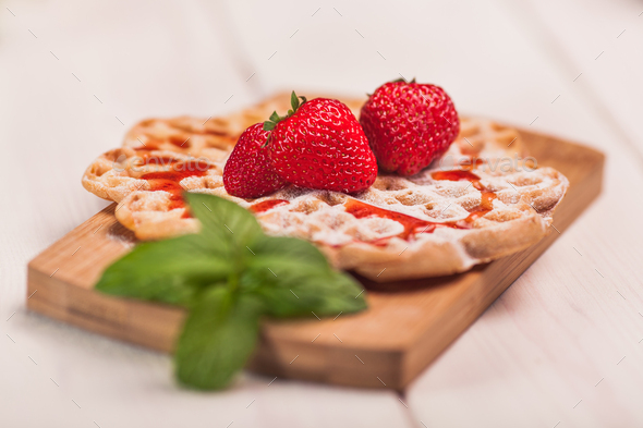 Waffles with strawberry on wooden plank - Stock Photo - Images