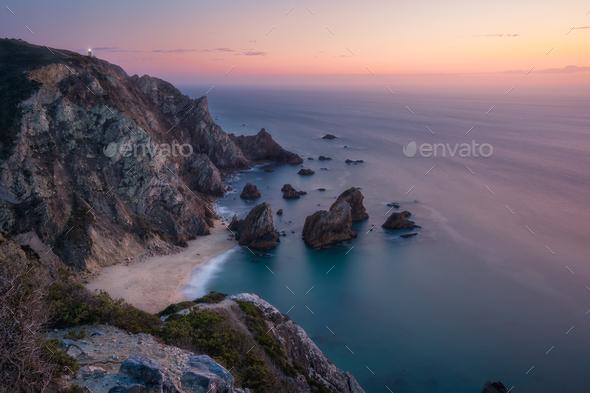 Sunset over a hidden surreal Praia Da Ursa Beach. Cabo Da Roca with light-house in background - Stock Photo - Images