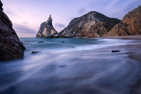 Epic Ursa Beach, Sintra, Portugal. Beach with waves and jugged rock peak in evening soft sunset - Stock Photo - Images