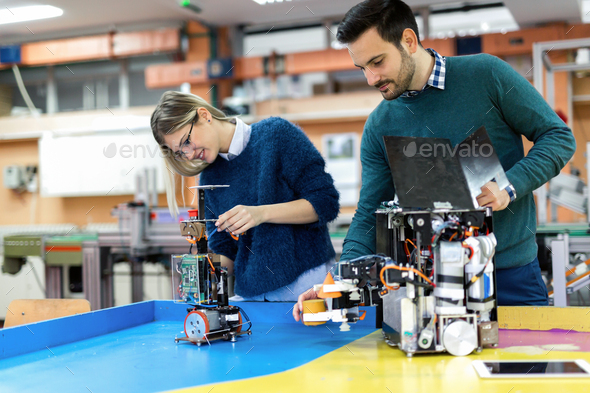 Young attractive students of mechatronics working on project - Stock Photo - Images