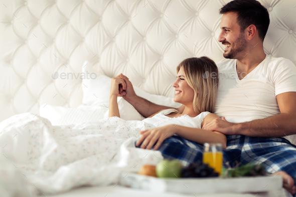 Romantic happy couple having breakfast in bed - Stock Photo - Images