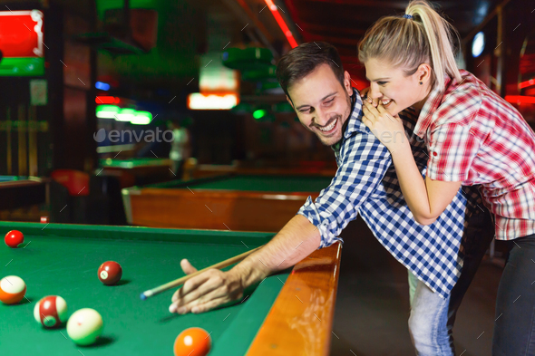 Young couple playing together pool in bar - Stock Photo - Images