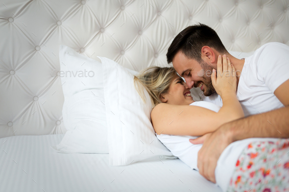 Handsome man and beautiful woman kissing on bed - Stock Photo - Images