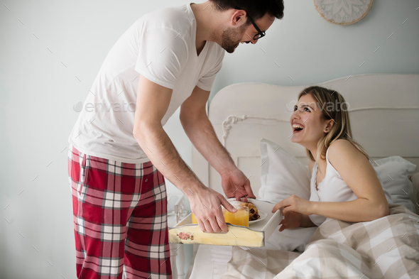 Atrractive man bringing breakfast to his beautiful girlfriend - Stock Photo - Images