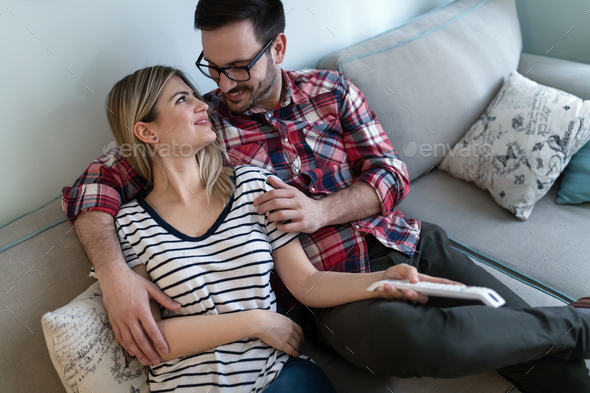 Young happy couple watching tv in living room - Stock Photo - Images