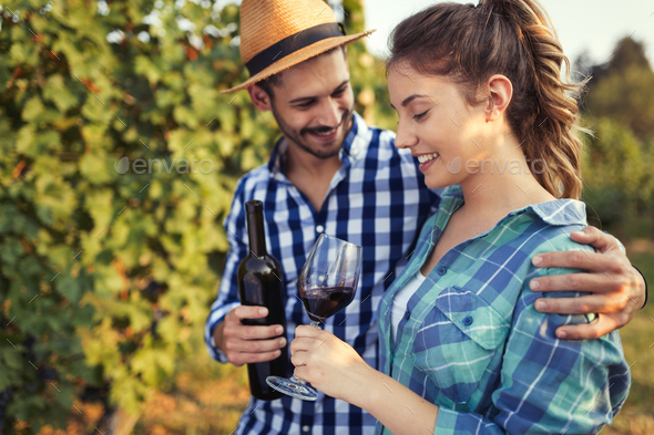 Woman and man in vineyard drinking wine - Stock Photo - Images